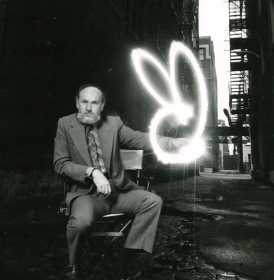 Art Paul sitting next to the playboy logo