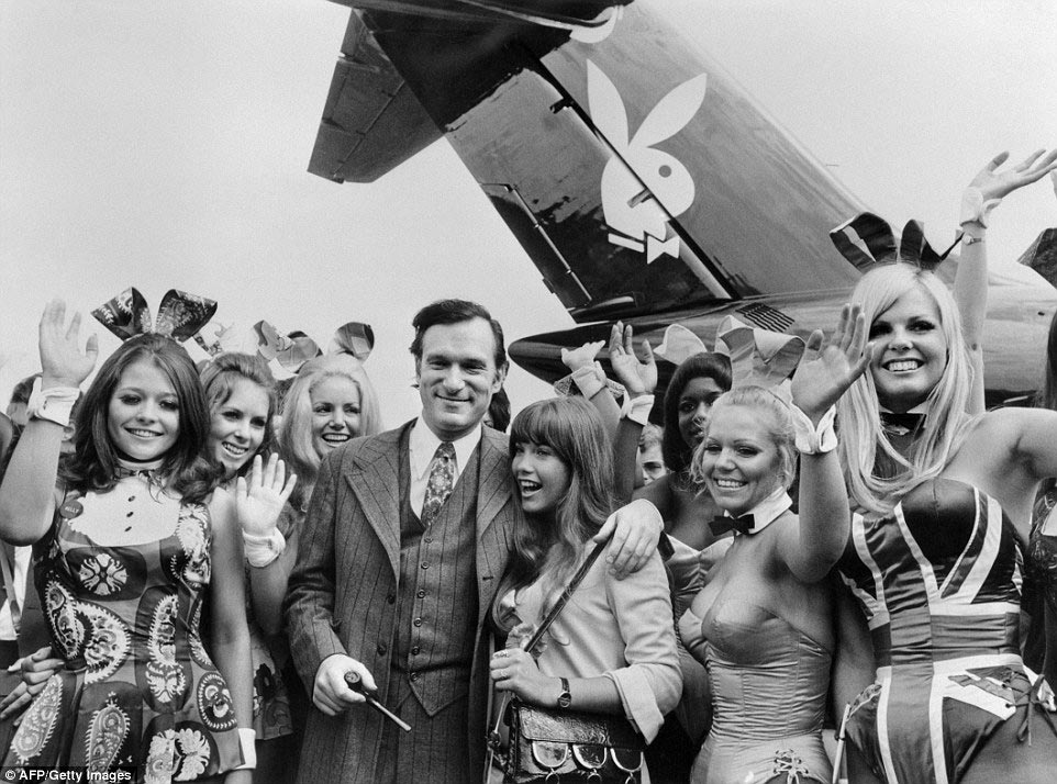 Hugh Hefner with Playboy bunnies in front of his private jet